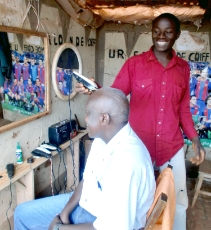 Burundi: Entrepreneur in Burundi who uses solar electricity in his kiosk, restaurant, for cutting hair and for charging cell phones and batteries. The owner received a subsidy and training from GIZ. Upon installation of the solar system, he hired two employees. <br />